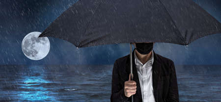 A man with a face mask is standing by the sea with an umbrella, the full moon can be seen in the background