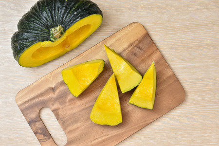 Sliced or cutted pumpkin for healthy menu on wooden kitchen top.