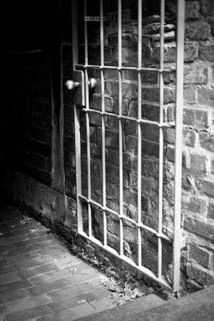 Open steel lattice door in front of a dark corridor in a German old town