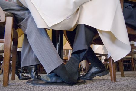 Man and Woman playing footsie under the table