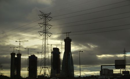 electrifying: Moody skies creating an electric glow as power lines tower above new construction in Madrid, Spain.  Growth in Madrid continues at an electrifying pace.