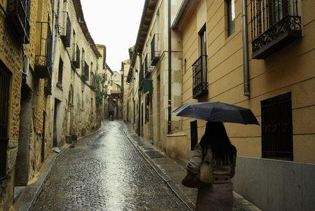 Lady Fu� bergauf auf einem Regen durchn�sst Gasse in Segovia, Spanien auf dem Weg zur Burg. Lizenzfreie Bilder