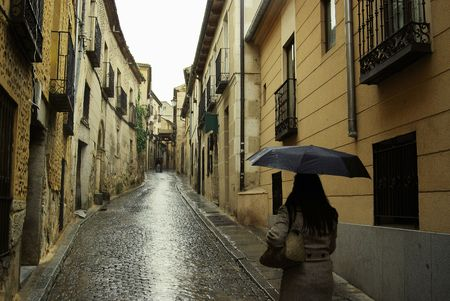 Lady walking uphill on a rain soaked alley in Segovia, Spain on her way to the castle.