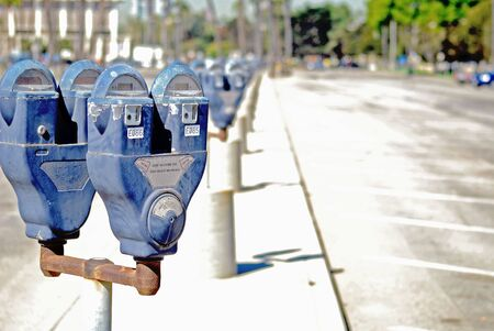doubled: Long row of old parking meters doubled up on every rusty pole. Stock Photo