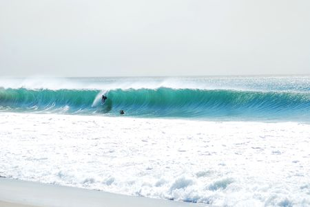 wade: Surfer being photographed by cameraman standing in the ocean.