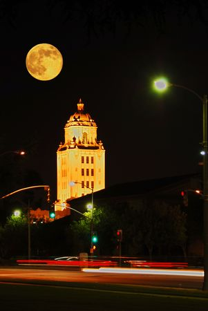 Full Moon rising over Beverly Hills City Hall in Los Angeles California, as vehicles streak by on Santa Monica Boulevard.
