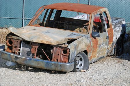 salvage yard: Total-loss Pickup Truck burnt and resting in a salvage yard.