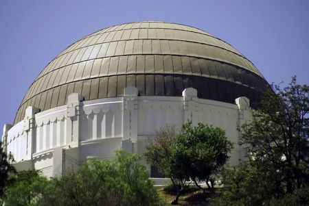 Roof panels on Griffith Park Observatory reflect the sun into the clear blue skies.
