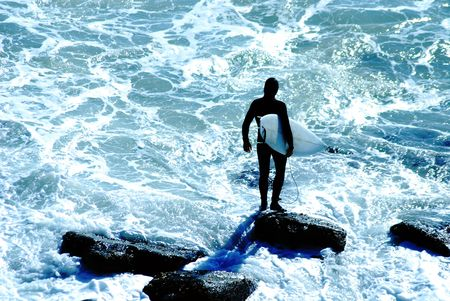Surfer in wetsuit holds tightly onto his surfboard before jumping into the cold Pacific Ocean in Malibu, California. Stock Photo