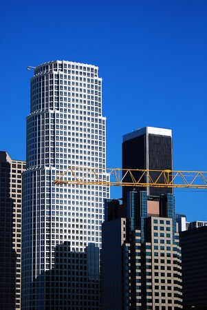 Construction crane busy at work in downtown Los Angeles, California on a clear sunny day.