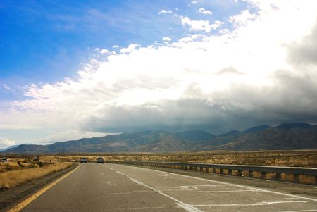 Interstate 10 provides magnificent desert views from California to Texas.  Storm clouds butt up against the mountains in this scene.