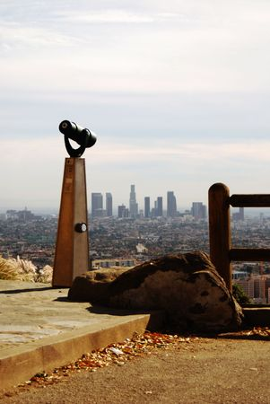 Telescope facing and pointing to downtown Los Angeles, California from a vista. 免版税图像