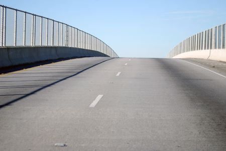 Drive over a one-way bridge, fenced in on both sides.