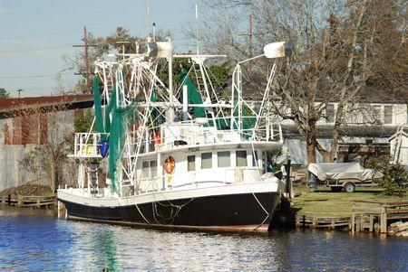 green boat: Shrimp Boat docked in the waterways of the bayou near New Orleans, Louisiana. Stock Photo