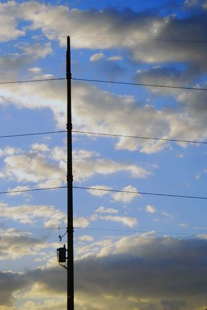 Transformer and power lines are held in place by pole and magnificent cloudscape at sunset. 免版税图像