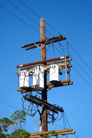 Drei Transformatoren mit drei Zeilen auf einer Telefon-polig Spannungsspitzen, wie Strom durch die Dr�hte Stromerzeugung Sitzung der Nachfrage f�r die Verbraucher von Nutzen.