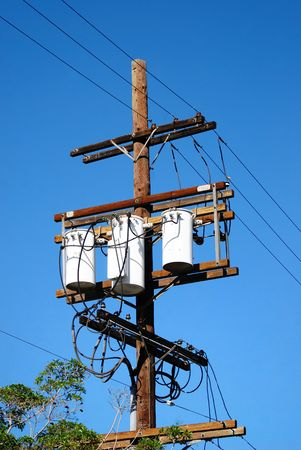 Three Transformers connected to three lines secured to a telephone pole as electricity surges through the wires generating power meeting the demand for consumers of utility. Stock Photo