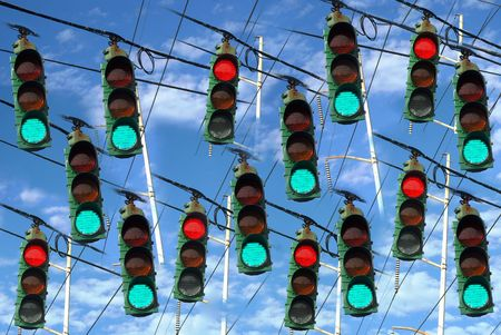 A collage of green and red lights hanging from wires over a beautiful cloudscape.