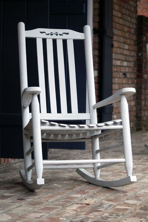 White rocking chair with a small little bow on the seatback to add a soft touch.