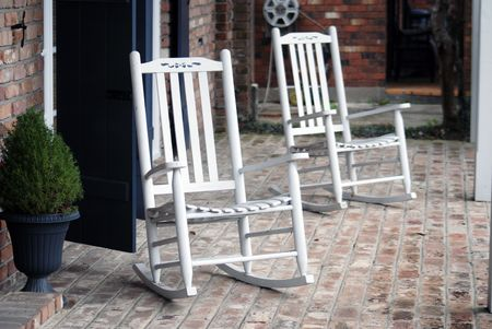 Two rocking chairs resting, southern style, on this front porch.