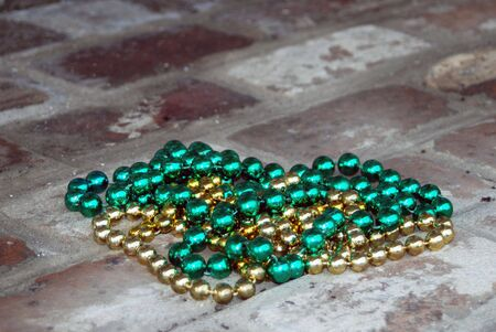 Green and gold Mardi Gras beads tossed onto a brick porch.