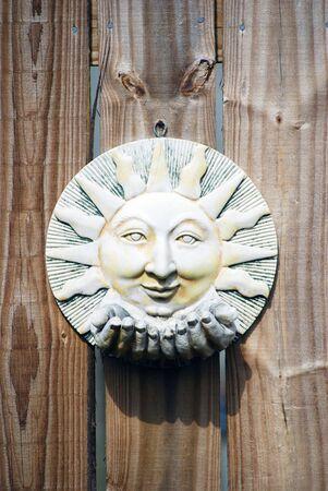 Sun worn sun ceramic hanging on a wooden fence.