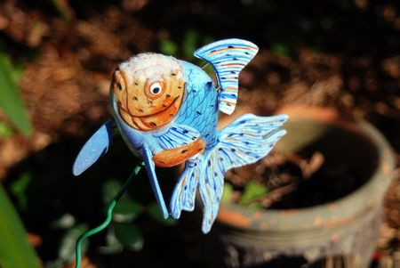 Blue and orange ceramic fish jumping out of a flower pot to get a breathe of fresh air...Gills not required.  This takes fly-fishing to a new extreme...better yet, how about �fish out of water�?