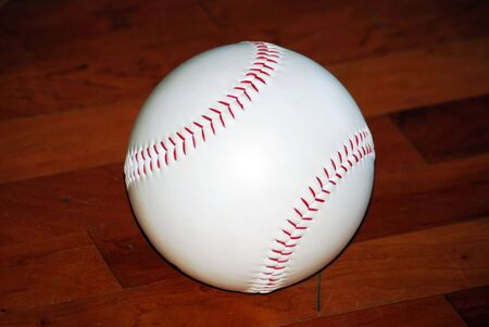 Close up of baseball sitting indoors on the hardwood floor.