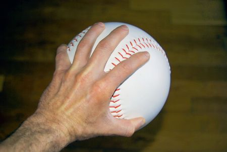 oversized: Hand gripping an oversized baseball making it difficult to pitch. Stock Photo