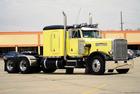 Yellow big rig parked in a mall parking lot.