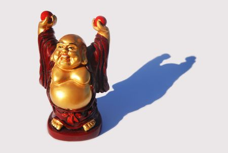 A victorious Buddha standing with both hands straight up in the air isolated over a white background casting a shadow. photo
