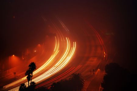 Vehicles driving in an early morning thick fog on the 101 Freeway in Los Angeles, California.