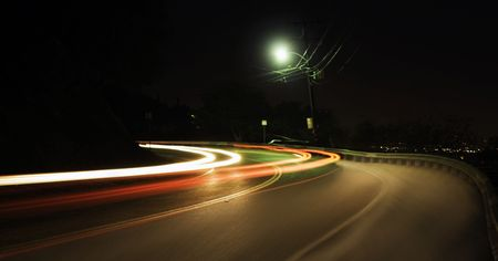 Cars driving a dangerous blindsided curve on at Mulholland Drive in Los Angeles Ca at night.