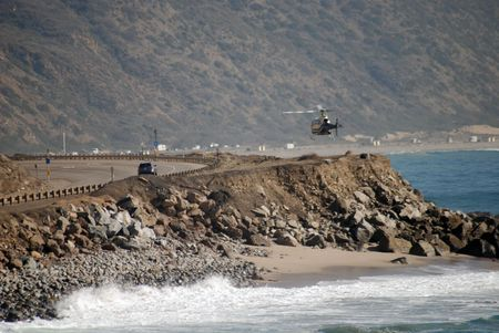 Helicopter in pursuit filming simulatenously in Malibu, California on Pacific Coast Highway in Los Angeles county on the Pacific Ocean.