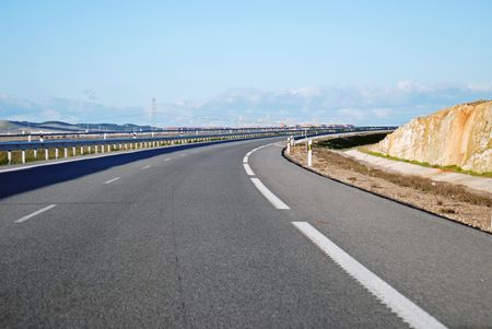 Driving on Highway A6 as it curves away from Madrid, Spain.