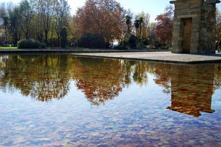 Leaves rest at the bottom of the reflecting pool as trees reflect off the water at the Debod Temple in Madrid, Spain, Europe.