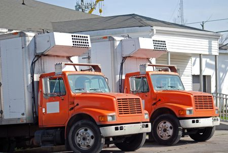 Two refrigerated trucks ready to go out on delivery runs.