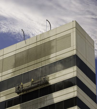 Window washers pressure washing building facade. 免版税图像 - 2757031