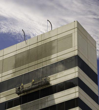 Window washers pressure washing building facade.