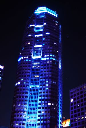 Corporate building lit up at night with a blue tinted light.