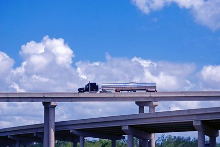 Tanker truck carrying liquid freight driving on interstate 310 over the swampy, marshland and interstate 10 on bridge near New Orleans, Louisiana. Stock Photo