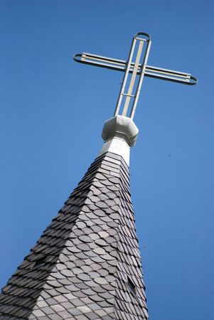 Cross atop a Cathedral in the blue sky. 免版税图像