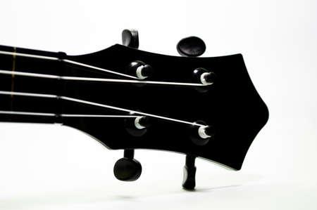 Fretboard of black ukulele on white background