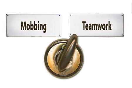 Straßenschild Richtung Teamwork versus Mobbing