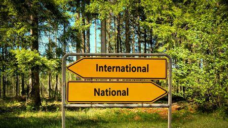Street Sign the DIrection Way to International versus National Фото со стока