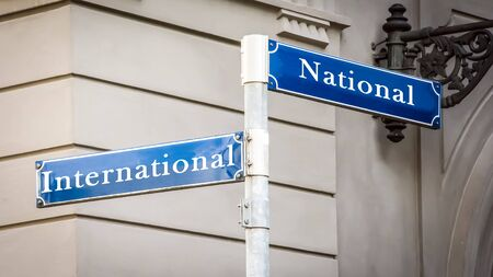 Street Sign the DIrection Way to International versus National 写真素材