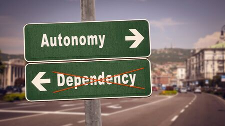 Street Sign the Direction Way to Autonomy versus Dependency Stock Photo