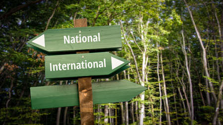 Street Sign the DIrection Way to International versus National Stock Photo