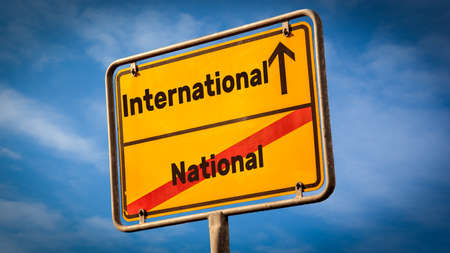 Street Sign the DIrection Way to International versus National Standard-Bild