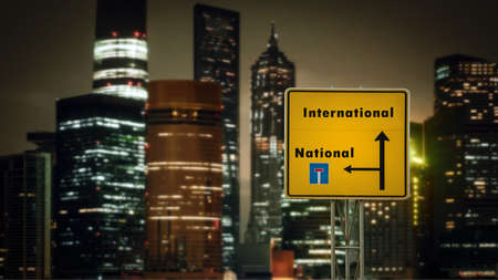 Street Sign the DIrection Way to International versus National Фото со стока